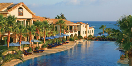 The resort's palm-fringed pool overlooks the sea
