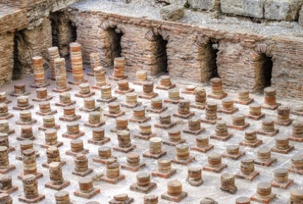 Archaeological ruins of brick vaults supporting the floor of the ancient Roman baths.