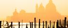 Gondolieri boats bob beneath a Venice sunset