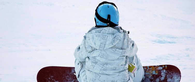 A snowboarder catching their breath