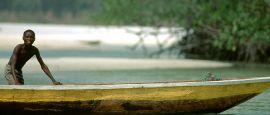 Boy fishing on canoe, Sierra Leone