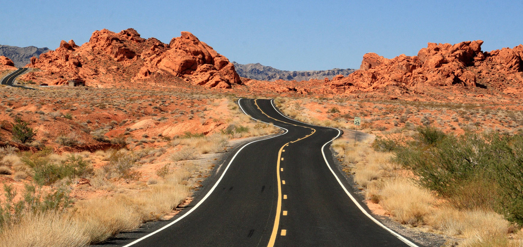 Blacktop winding through red rocks near Valley of Fire State Park in Nevada